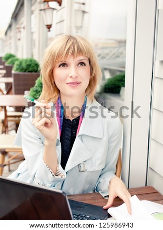 Young businesswoman with laptop outdoor - stock photo