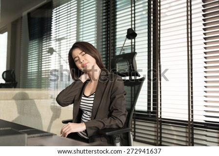Young businesswoman with neck pain sitting at office desk - stock photo