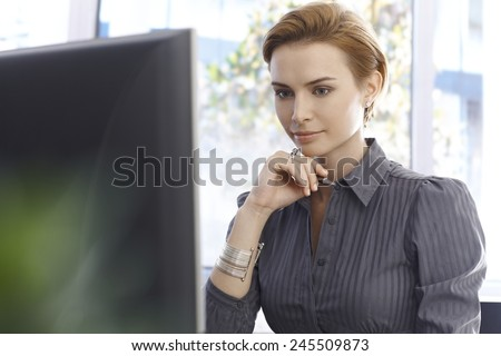 Young businesswoman working with computer, concentrating. - stock photo