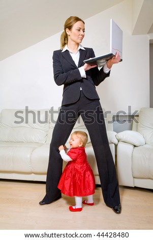 Young businesswoman working with laptop and her baby daughter crying - stock photo