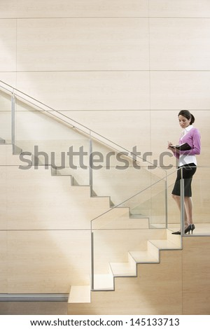 Young businesswoman writing in diary while standing by glass railing on steps in office - stock photo