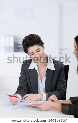 Young businesswomen discussing in meeting at desk in office - stock photo