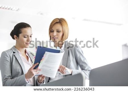 Young businesswomen discussing over book in office - stock photo