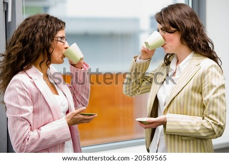 Young businesswomen having break at office drinking coffee and talking. - stock photo