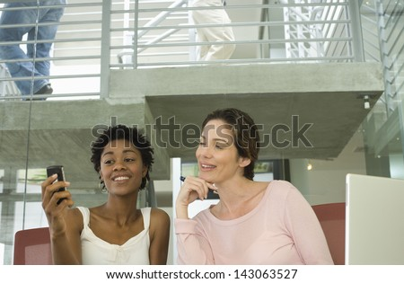 Young businesswomen reading text message on cell phone in office - stock photo