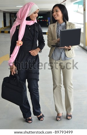 Young businesswomen sharing info on laptop and smile - stock photo