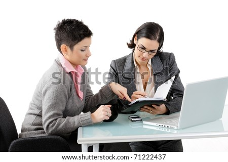 Young businesswomen sitting at office desk, working and talking. Isolated on white background.? - stock photo