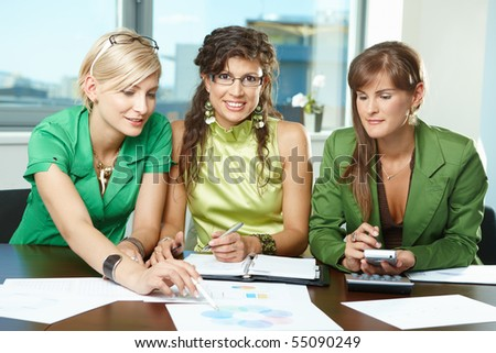 Young  businesswomen sitting at table in meeting room, discussing charts on table, looking at camera, smiling. - stock photo