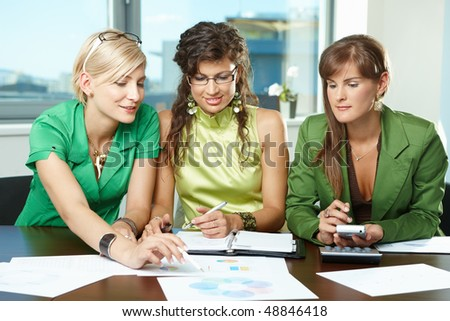 Young  businesswomen sitting at table in meeting room, discussing charts on table, smiling. - stock photo