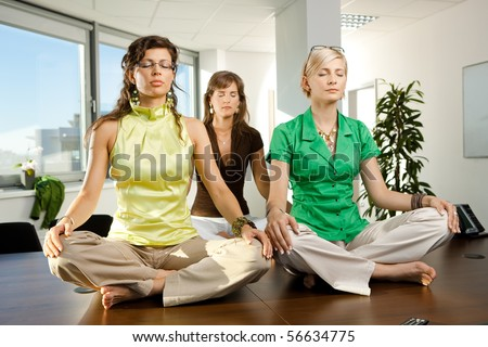 Young businesswomen sitting in yoga position on meeting room table. - stock photo