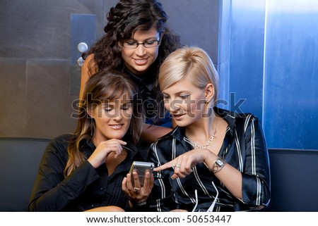 Young businesswomen sitting on couch at office lobby, looking at smart phone, smiling. - stock photo