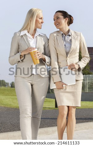 Young businesswomen with disposable cup and laptop walking on street - stock photo