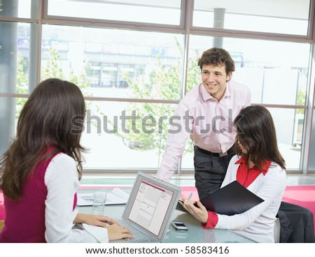 Young businesswomen working in office, using laptop computer, writing notes. Smiling businessman leaning on desk. - stock photo