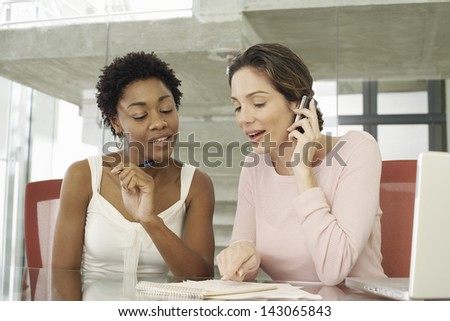 Young businesswomen working together at table - stock photo