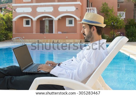 Young bussines man working on his lap top by the pool while on vacation  wearing straw hat - stock photo