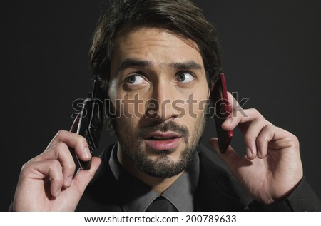 Young busy businessman talking into two mobile phones - stock photo