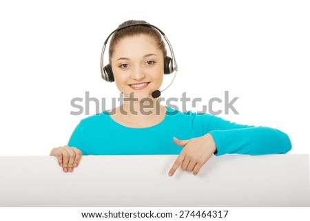 Young call center woman pointing on billboard. - stock photo