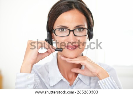 Young callcenter employee in blue blouse talking on headphones while looking at you cheerfully - stock photo