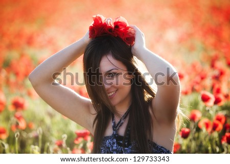 Young candid girl surrounded and playing with poppies. - stock photo