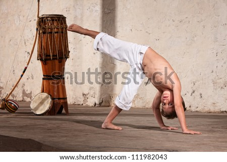 Young capoeria martial artist next to berimbau on floor - stock photo