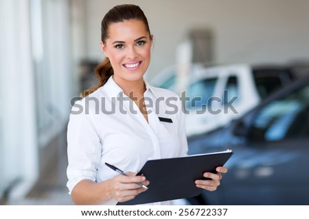 young car saleswoman holding clipboard in showroom - stock photo