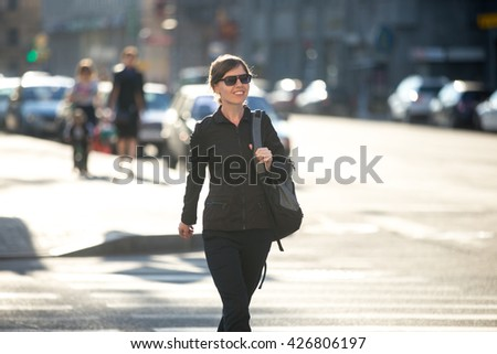 Young carefree smiling woman with backpack crossing the road at pedestrian crosswalk, walking in sunny European city street in summer, blurred cars on the background - stock photo