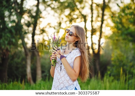 Young carefree teenage girl in sunglasses portrait. Stylish lifestyle portrait. Girl holding a bouquet of wildflowers. - stock photo