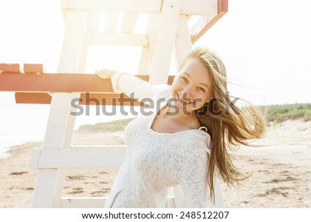 Young carefree woman with lifeguard chair on Atlantic beach in Prince Edward Island, Canada. - stock photo