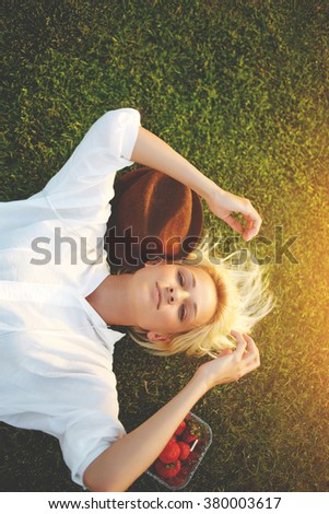 Young carefree woman with stylish hat lying down on park green grass during free time in summer day, charming young female student resting on a lawn before the beginning of lectures at the University - stock photo