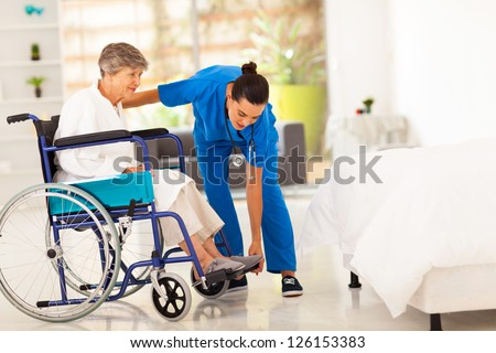 young caregiver helping elderly woman on wheelchair - stock photo