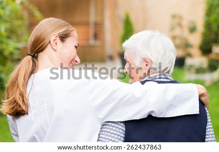 Young carer walking with the elderly woman in the park - stock photo