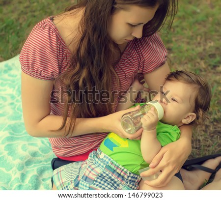 Young caring mother gives son drink water bottles on lawn in summer park - stock photo