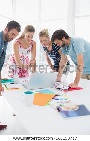 Young casual business people using laptop together in a bright office - stock photo
