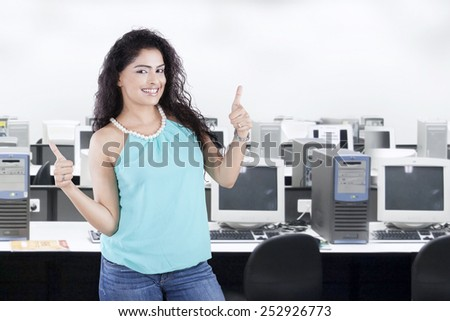 Young casual businesswoman with curly hair standing in the office while showing thumbs up - stock photo