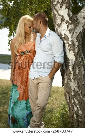 Young casual caucasian man embracing attractive blonde female outdoor. Leaning against tree, hands in pocket. - stock photo