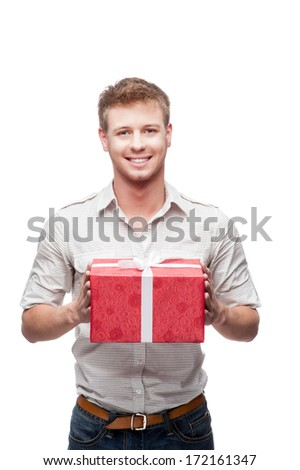 young casual caucasian man holding red christmas gift isolated on white background - stock photo