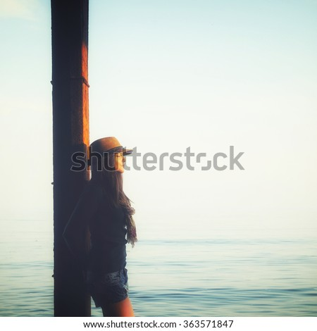 Young casual girl standing with closed eyes, relaxing under the pier in a sea water, enjoy sunset light and breathing fresh air. - stock photo