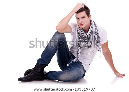 young casual happy man seated on studio, on white background - stock photo