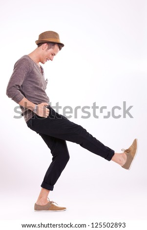 young casual man goofing around, standing on one leg, looking down with his hands in his pockets, on a light background - stock photo