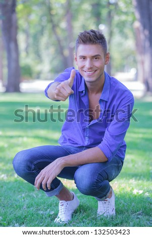 young casual man in a crouched position in the park is showing thumb up gesture and smiling to the camera - stock photo