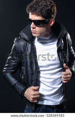 young casual man in jacket portrait, isolated over black background - stock photo