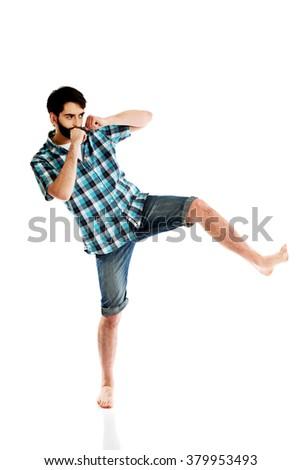 Young casual man kicking. - stock photo