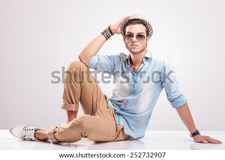 Young casual man lying on the floor, holding his hand on his hat, looking at the camera. - stock photo
