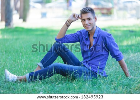 young casual man posing in the grass in a seated pose, smiling at the camera - stock photo