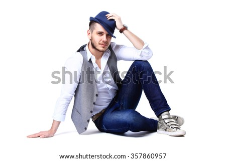 young casual man posing on the floor and smiling to the camera, against white background - stock photo