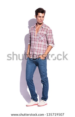 young casual man posing with hands in pockets and looking away from the camera - stock photo