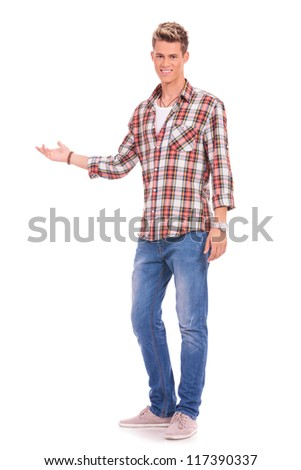 Young casual man presenting something and looking at the camera, with a smile on his face - stock photo
