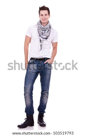 young casual man wearing boots, jeans and scarf looking at the camera on white background - stock photo