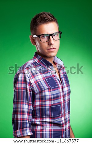young casual man with eyeglasses looking at the camera, against a green background - stock photo