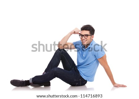 young casual man with eyeglasses posing on the floor and smiling to the camera, against white background - stock photo